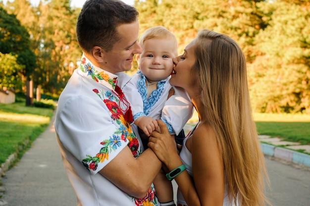 Szczęśliwi rodzice trzymający chłopca ubranego w haftowaną koszulę