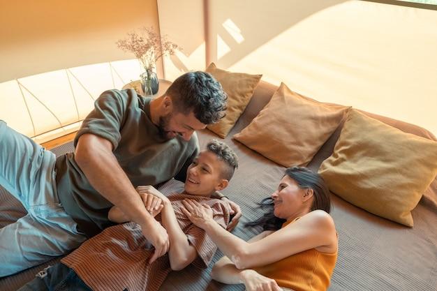 Szczęśliwi rodzice tykają swojego nastoletniego syna podczas relaksu na łóżku