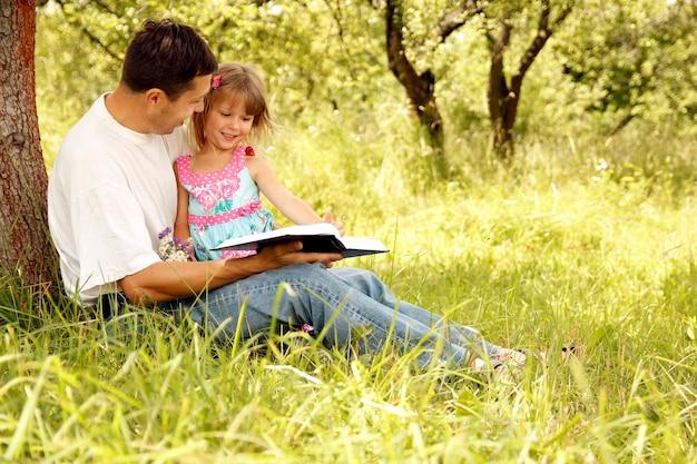Szczęśliwi rodzice z dzieckiem czytają biblię w parku przyrody