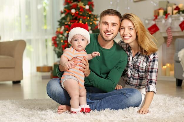 Szczęśliwi rodzice z dzieckiem w udekorowanym pokoju na boże narodzenie