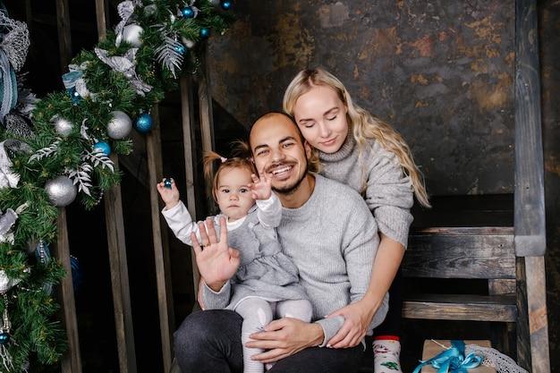 Szczęśliwi rodzice z dzieckiem w urządzonym pokoju na boże narodzenie