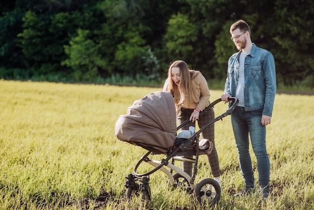 Szczęśliwi rodzice z miłością i czułością patrzą na swoje dziecko leżące w wózku