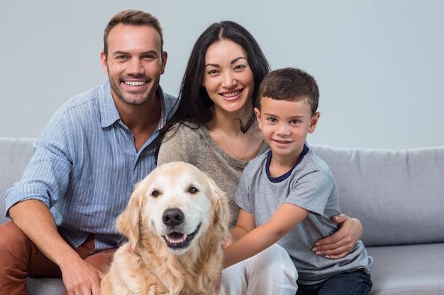 Szczęśliwi rodzice z synem i zwierzęciem domowym w salonie