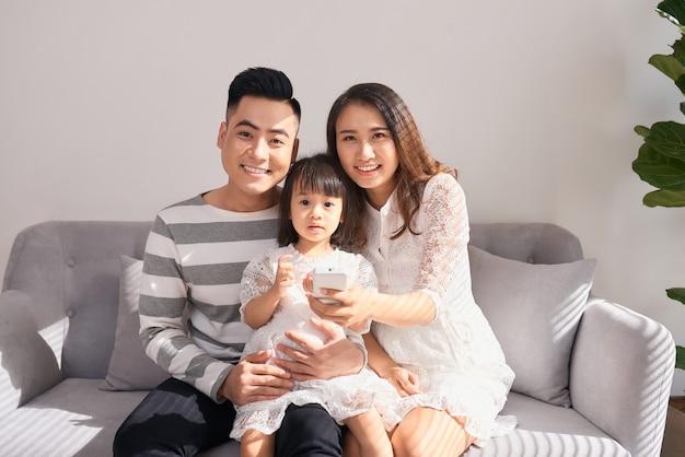 Szczęśliwi rodzice z uroczą małą córeczką siedzącą na kanapie i uśmiechającą się do kamery