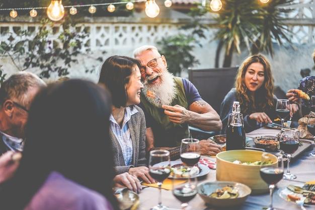 Szczęśliwi rodzinni ludzie bawią się przy kolacji z grilla - wielorasowi przyjaciele jedzą przy grillu