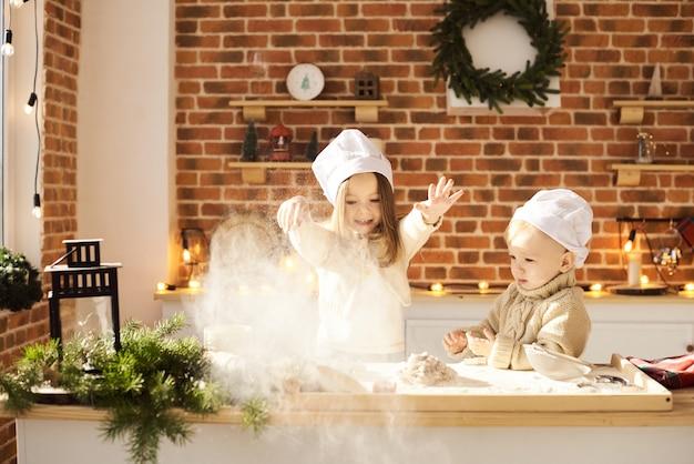 Szczęśliwi rodzinni śmieszni dzieciaki przygotowywają ciasto, bawić się z mąką w kuchni