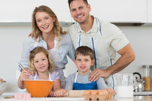 Szczęśliwi rodzinni wypiekowi ciastka przy kuchennym kontuarem