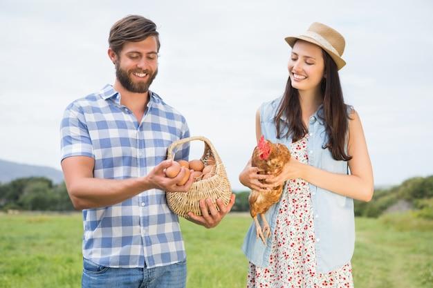 Szczęśliwi rolnicy trzyma kurczaka i jajka