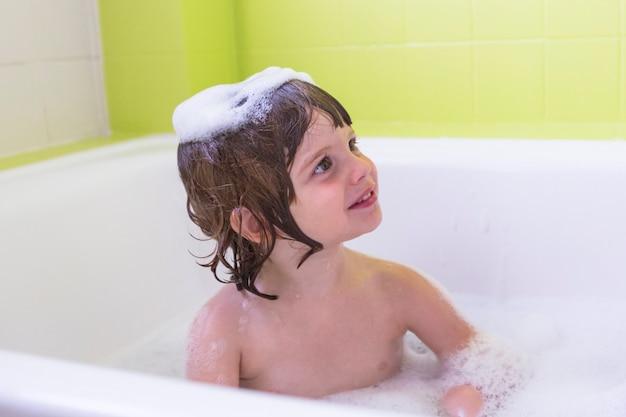 Szczęśliwi roześmiani siostra dzieciaki kąpać się bawić się z piankowymi bąblami. małe dzieci w wannie. rodzinny styl życia w pomieszczeniu