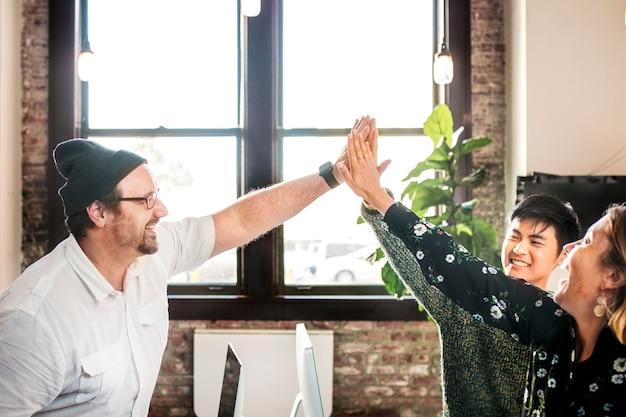 Szczęśliwi, różnorodni koledzy ze start-upu, którzy przybijają piątkę