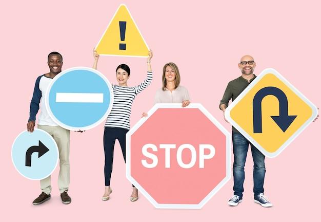 Szczęśliwi różnorodni ludzie posiadający znaki drogowe