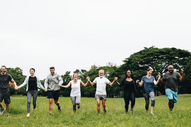 Szczęśliwi różnorodni ludzie trzyma ręki w parku
