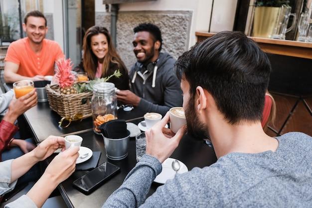 Szczęśliwi różnorodni przyjaciele jedzący i pijący na świeżym powietrzu w restauracji w stylu vintage - główny nacisk na właściwą głowę mężczyzny