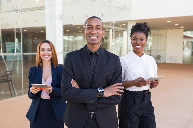 Szczęśliwi rozochoceni ludzie biznesu pozuje w biurowym korytarzu