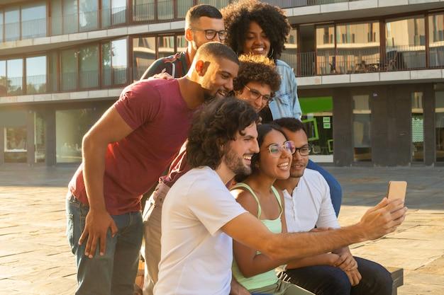 Szczęśliwi rozochoceni międzyrasowi ludzie bierze grupowego selfie
