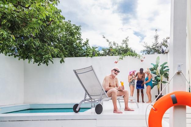 Szczęśliwi seniorzy na imprezie na basenie - starsi przyjaciele na imprezie przy basenie