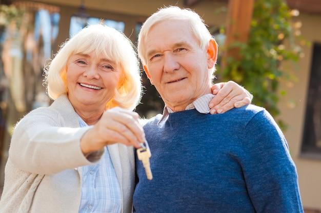 Szczęśliwi seniorzy. szczęśliwa para seniorów, która łączy się ze sobą i uśmiecha, podczas gdy kobieta trzyma klucze w dłoni