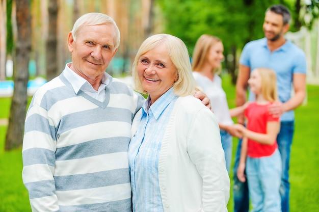Szczęśliwi seniorzy z rodziną. szczęśliwa para seniorów, która łączy się i patrzy w kamerę, podczas gdy inni członkowie rodziny stoją w tle