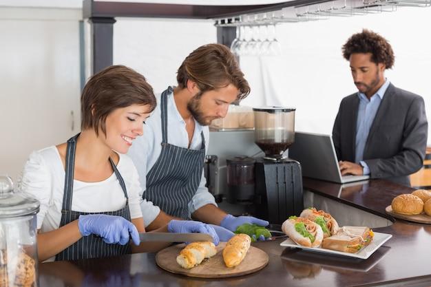 Szczęśliwi serwery przygotowywający kanapki wpólnie