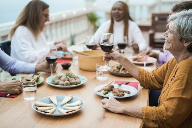 Szczęśliwi starsi ludzie dopingujący czerwonym winem podczas kolacji z grilla na świeżym powietrzu - skoncentruj się na prawej twarzy kobiety