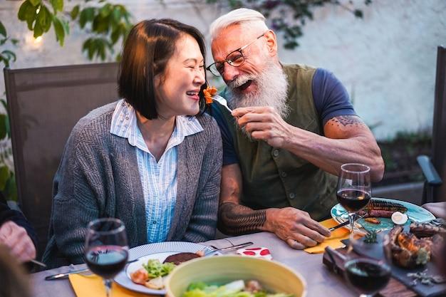 Szczęśliwi starsi ludzie ma zabawę przy grilla obiadem
