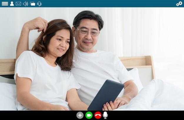 Szczęśliwi starsi ludzie rozmawiający przez internet wideorozmowy w domu