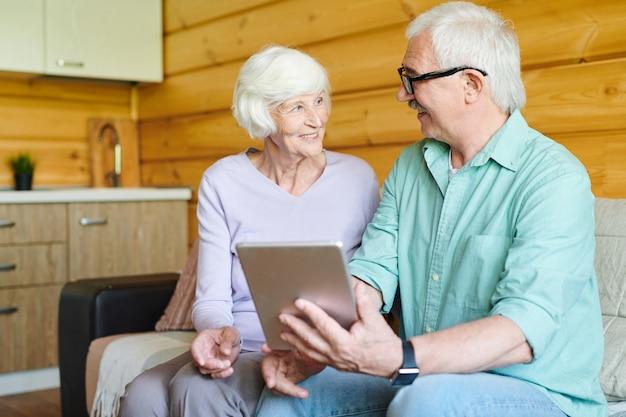Szczęśliwi starsi małżonkowie w codziennym stroju dyskutują na temat danych online lub wideo na tablecie, siedząc na kanapie w salonie