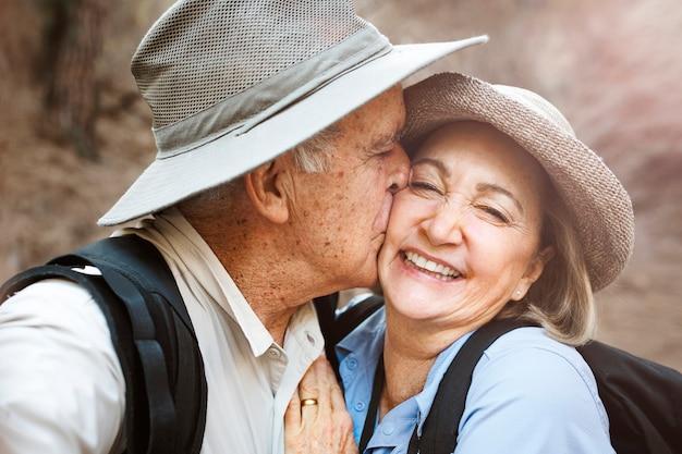 Szczęśliwi starsi partnerzy robiący selfie w lesie