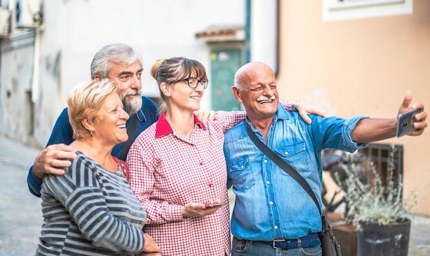 Szczęśliwi starsi przyjaciele biorący selfie na placu podczas podróży - emeryci bawią się razem z telefonem komórkowym - koncepcja pozytywnego stylu życia osób starszych