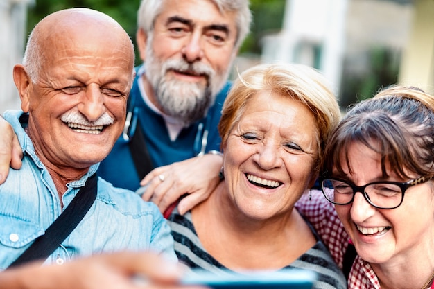 Szczęśliwi starsi przyjaciele robiący selfie wokół ulicy starego miasta
