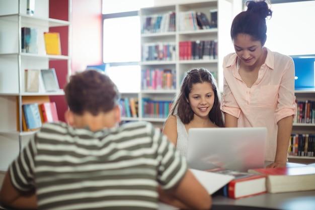 Szczęśliwi studenci korzystający z laptopa w bibliotece