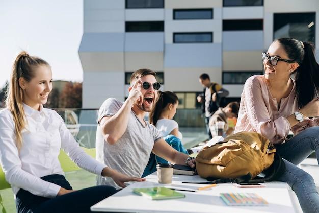 Szczęśliwi studenci pracują i uczą się przy stole na świeżym powietrzu