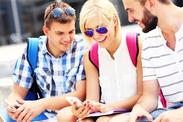 Szczęśliwi studenci siedzący na schodach ze swoimi smartfonami