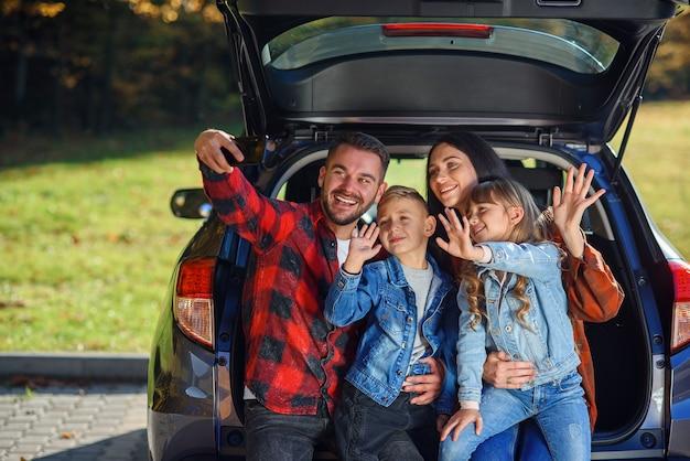 Szczęśliwi, stylowi rodzice ze swoimi uroczymi uroczymi dziećmi robią śmieszne selfie na smartfonie, siedząc w bagażniku.