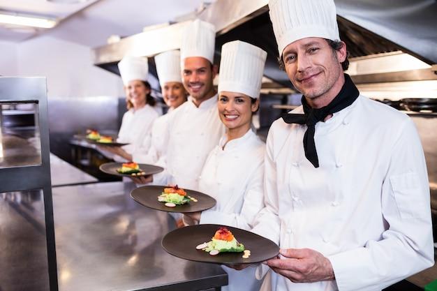 Szczęśliwi szefowie kuchni prezentują swoje talerze z jedzeniem