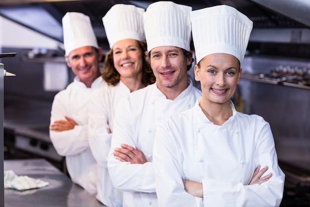 Szczęśliwi szefowie kuchni zespalają się pozycję wpólnie w handlowej kuchni