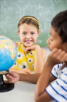 Szczęśliwi szkolni dzieciaki z kulą ziemską w sala lekcyjnej