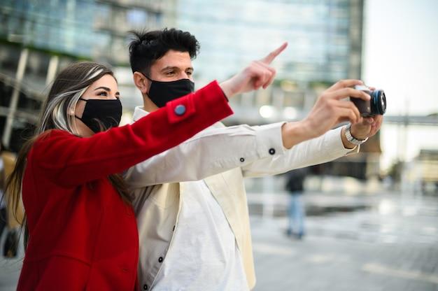 Szczęśliwi turyści z maskami na krukowicę lub koronawirusa para spacerująca razem po mieście i fotografująca ciekawe miejsce