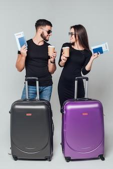 Szczęśliwi turyści z torbą podróżną i filiżanką kawy na szarym tle