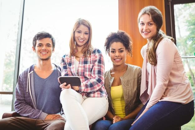 Szczęśliwi ucznie siedzi na kanapie używać telefon komórkowego