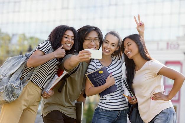 Szczęśliwi ucznie stoi selfie i robią na zewnątrz