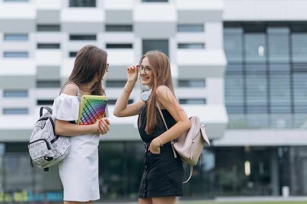 Szczęśliwi uczniowie chodzą w szkole. grupa studentów, spacer przed nowoczesnym budynkiem, przyjemnie rozmawia