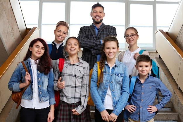 Szczęśliwi uczniowie i nauczyciel stojący na szkolnych schodach