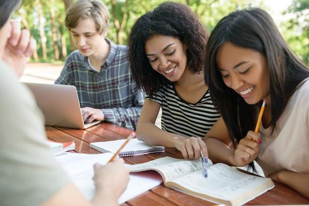 Szczęśliwi uczniowie siedzący i studiujący na zewnątrz podczas rozmowy.