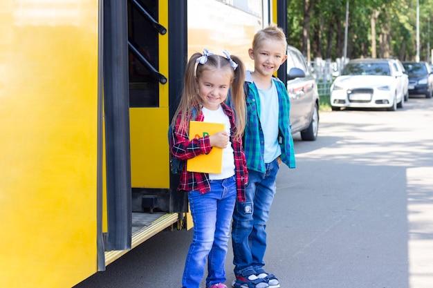 Szczęśliwi uczniowie z plecakami wysiadają ze szkolnego autobusu.