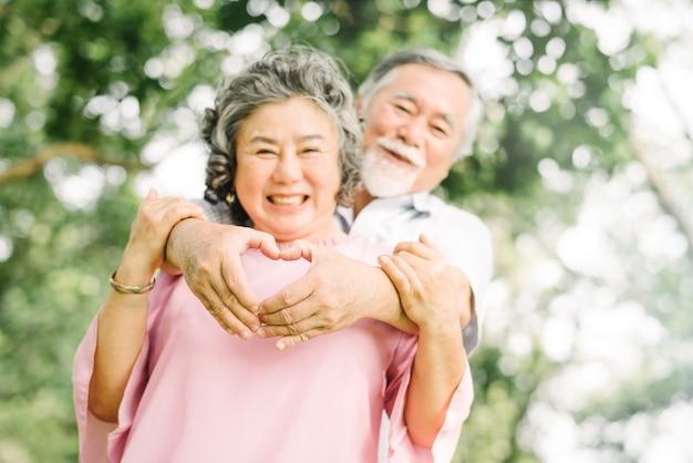 Szczęśliwi uśmiechi starsza azjatycka para cieszy się ilość czas przy parkiem