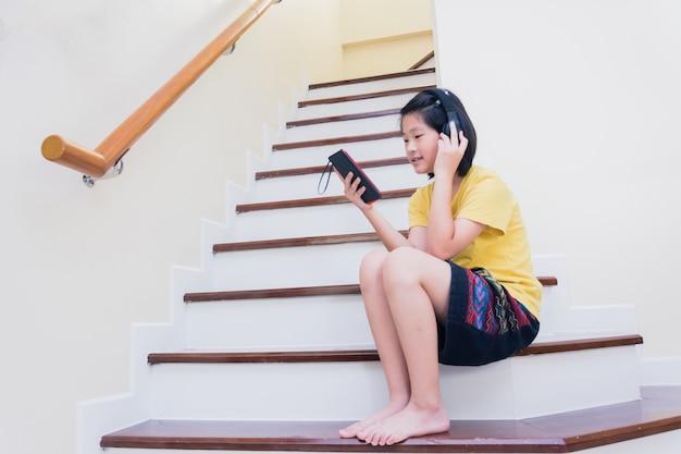 Szczęśliwi uśmiechnięci azjata dzieciaki na drabinowym słuchaniu muzyka od mądrze telefonu z słuchawką, technologia przeciw