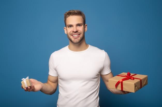 Szczęśliwi uśmiechnięci mężczyzna mienia prezenty odizolowywający na błękicie