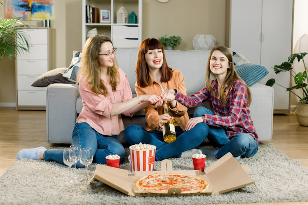 Szczęśliwi uśmiechnięci młoda kobieta przyjaciele je pizzę, popkorn i otwiera bucik wina przyjęcie w domu. impreza z pizzą, przyjaźń kobiet