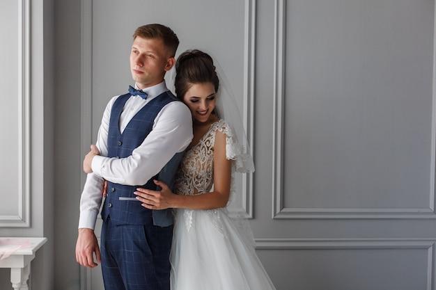 Szczęśliwi uśmiechnięci nowożeńcy w pokoju hotelowym